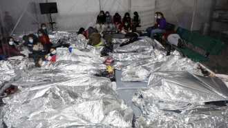 Kids lay in a crowded CBP shelter in Texas