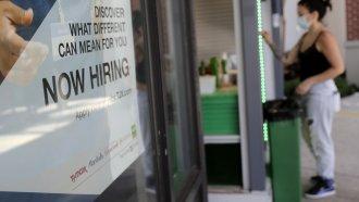 A store displays a hiring sign