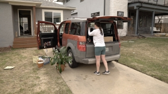 Woman packs items in a car