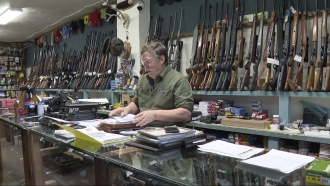 Gun shop owner sorts paperwork.