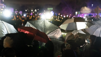 Demonstrators use umbrellas as shields against police during a clash outside the Brooklyn Center Police