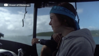Teenager sails a boat.
