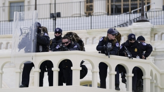 Police keep a watch on demonstrators who tried to break through a police barrier at the Capitol in Washington.