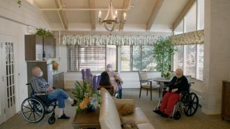 Seniors sit in a nursing home.