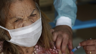 A woman receives her second dose of the Sinovac vaccine in Brazil.