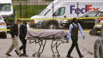 A body is wheeled away after mass shooting in Indianapolis.