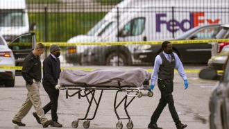 A body is taken from the scene where multiple people were shot at a FedEx Ground facility in Indianapolis