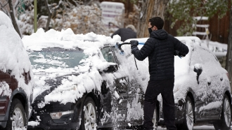 A motorist clears snow from his car after a storm.