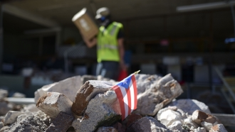 A Puerto Rican flag hangs within the rubble after an earthquake Tuesday, Jan. 7, 2020