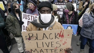 Man holds a sign at a protest.