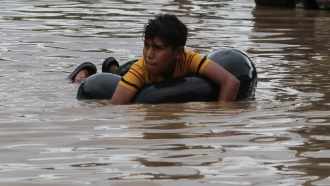 A child floats on an inner tube in a flooded street in the aftermath of Hurricane Eta inHonduras, Friday, Nov. 6, 2020