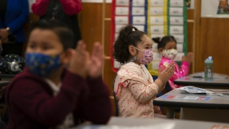 File photo, first graders applaud while listening to their teacher in a classroom