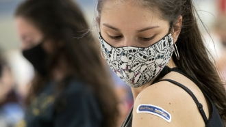 Kent State University student Regan Raeth of Hudson, Ohio, looks at her vaccination bandage.