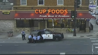Surveillance video of Minneapolis police officers attempting to take George Floyd into custody.