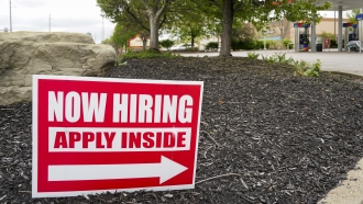 "A ""Now Hiring"" sign posted outside and American business."