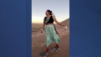 Woman skateboards in a desert