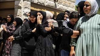 Mourners react during a funeral of a child killed during the attacks in Israel.