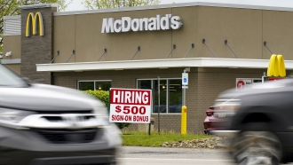 A hiring sign offers a $500 bonus outside a McDonalds restaurant.