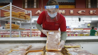 A worker restocks chicken in the meat product section at a grocery store in Dallas, Texas