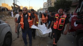 Palestinians carry the body of a child found in the rubble of a house in the Gaza Strip