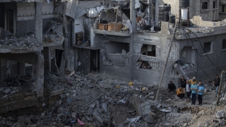 Palestinians inspect their destroyed houses following overnight Israeli airstrikes in northern Gaza Strip.