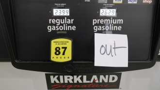 A note posted at a gas pump indicates the pump is out of premium gasoline at a Costco Warehouse fuel station in Mis