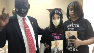 Attorney Benjamin Crump with the daughter and sister of Andre Hill.
