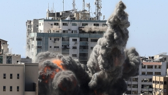 Smoke billows from a building housing international media, including The Associated Press, after an Israeli airstrike.