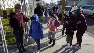 An assistant principal welcomes students at an elementary school