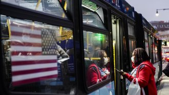 People wear protective masks during the coronavirus pandemic while boarding a bus.