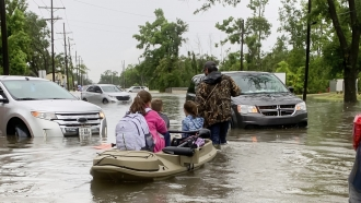 Parents use boats to pick up students from schools after nearly a foot of rain fell in Lake Charles, La.