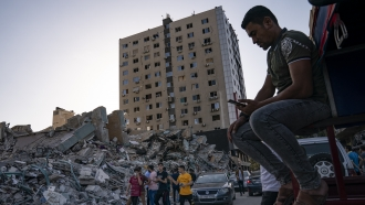 People gather to view the rubble of the al-Jalaa building following a cease-fire between Gaza's Hamas rulers and Israel.