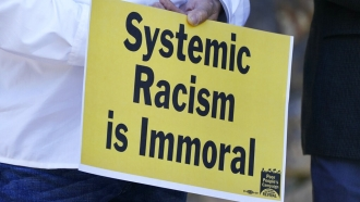 Pastor Jose Rodriquez holds a sign against systemic racism