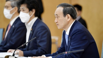 Japanese Prime Minister Yoshihide Suga, right, attends the government task force meeting for the COVID-19 measures