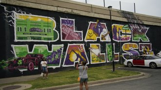 Visitors photograph Black Wall Street mural