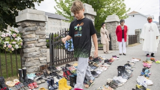 A boy puts down tobacco as a tribute to all the victims of the residential school system