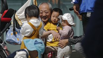 An elderly man plays with children near a commercial office building in Beijing, China