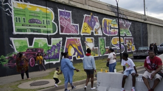 """People by a """"Black Wall Street"""" mural in the Greenwood district during centennial commemorations of the Tulsa Race Massacre"""