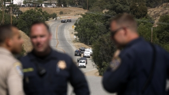 Law enforcement authorities close off a road during an investigation for a shooting at fire station 81 in Santa Clarita, CA