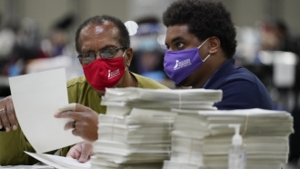 Two workers examine 2020 ballots.