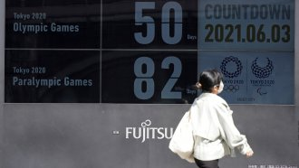 People walk past the countdown clock for the Tokyo 2020 Olympic and Paralympic Games