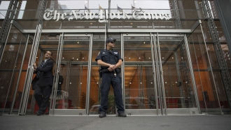 A police officer stands outside The New York Times building in New York.