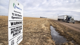 A grain truck drives past a Keystone pipeline pumping station