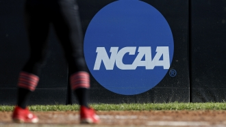 College athlete stands near the NCAA logo during a softball game.