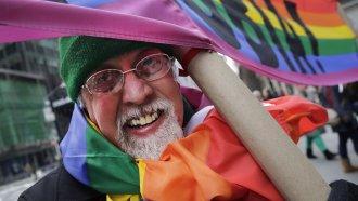 Gilbert Baker, creator of the rainbow pride flag, carries flag