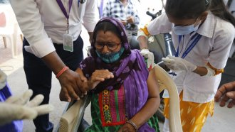 A disabled woman gets a dose of India's version of the AstraZeneca vaccine.