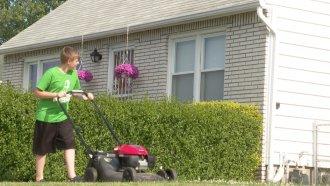 A teen mows a lawn.