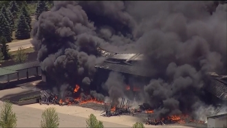 A chemical plant on fire with large plumes of smoke rising.
