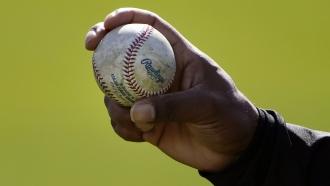 An MLB pitcher shows his grip on a baseball.