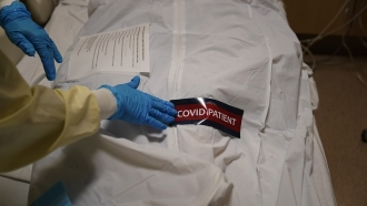 """A hospital worker places a """"COVID Patient"""" sticker on a body bag holding a deceased patient"""